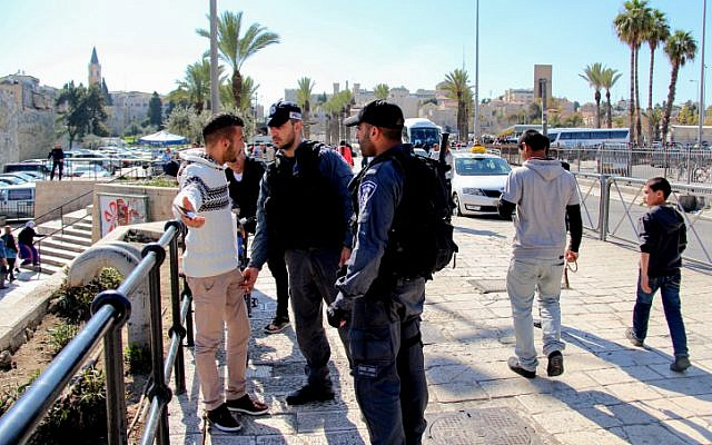 Illustrative: Israeli police officers search a Palestinian man at Damascus Gate in Jerusalem on February 26, 2016. (Haytham Shtayeh/Flash90)
