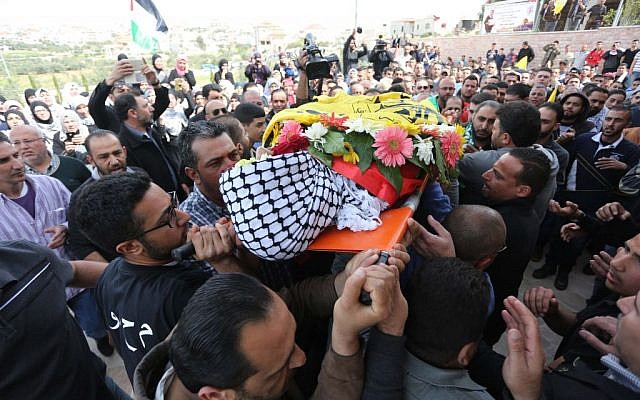 Palestinian mourners chant slogans while carrying the body of Mahmoud Shalan, 17, during his funeral in the West Bank village of Deir Debwan, near Ramallah, March 2, 2016. (Photo by Flash90)