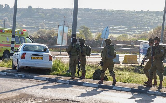 Israeli security forces approach the car of a Palestinian attacker at the scene of a car-ramming attack near the Gush Etzion Junction in the West Bank on March 4, 2016. (Gershon Elinson/Flash90)