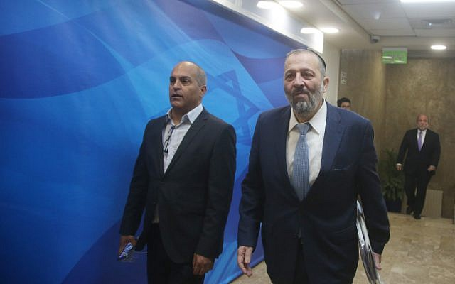 Interior Minister Aryeh Deri (R) arrives at the Prime Minister's Office in Jerusalem for the weekly cabinet meeting, March 6, 2016. (Marc Israel Sellem/Pool)