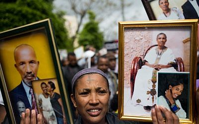 Israelis who immigrated from Ethiopia hold up family photos of loved ones who remain in Ethiopia, during a protest to bring the rest of the Falashmura to Israel, in Jerusalem, on March 20, 2016. (Yonatan Sindel/Flash90)