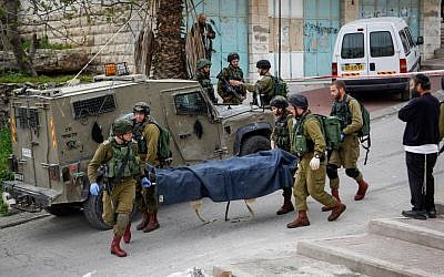 Israeli soldiers remove the body of a Palestinian man who stabbed a soldier in the West Bank city of Hebron on March 24, 2016. The Palestinian was shot at the scene after stabbing and wounding an Israeli soldier. (Wissam Hashlamon/Flash90)