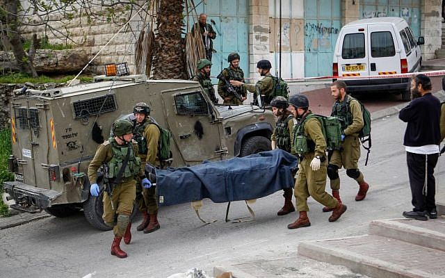 Israeli soldiers remove the body of a Palestinian man shot after he stabbed and wounded a soldier in the West Bank city of Hebron on March 24, 2016. (Wissam Hashlamon/Flash90)