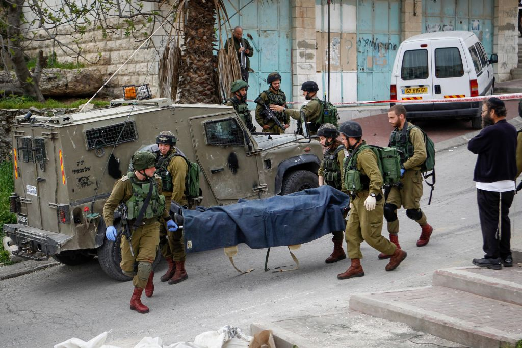 Israeli soldiers remove the body of a Palestinian man who stabbed a soldier in the West Bank city of Hebron on March 24, 2016. The Palestinian was shot at the scene after stabbing and lightly wounding an Israeli soldier. (Wissam Hashlamon/Flash90)