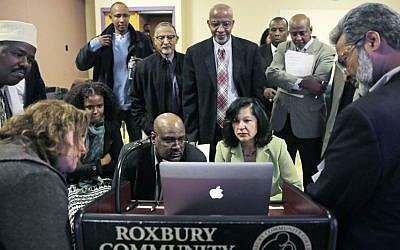 Muslim, Christian, minority and government leaders fix their eyes on a laptop screen showing a video as part of a federal pilot program called 'Countering Violent Extremism,' at Roxbury Community College in Boston, March 31, 2015. (AP/Charles Krupa, File)