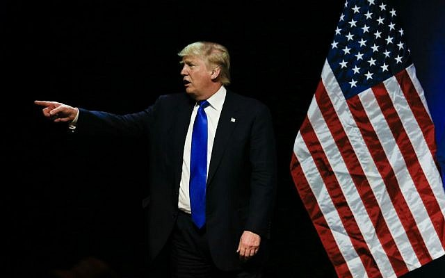 Republican presidential candidate Donald Trump points towards a demonstrator in the audience as he speaks at an election rally in Kansas City, Missouri, Saturday, March 12, 2016. (AP Photo/Nati Harnik)