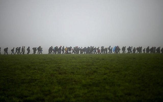 In this Oct. 15, 2015 file photo, a group of migrants make their way over a meadow after crossing the border between Austria and Germany in Wegscheid near Passau, Germany. (AP Photo/Matthias Schrader, file)