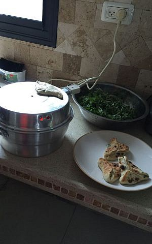 The electric pita maker, also used for frying and baking the sambussak (Jessica Steinberg/Times of Israel)