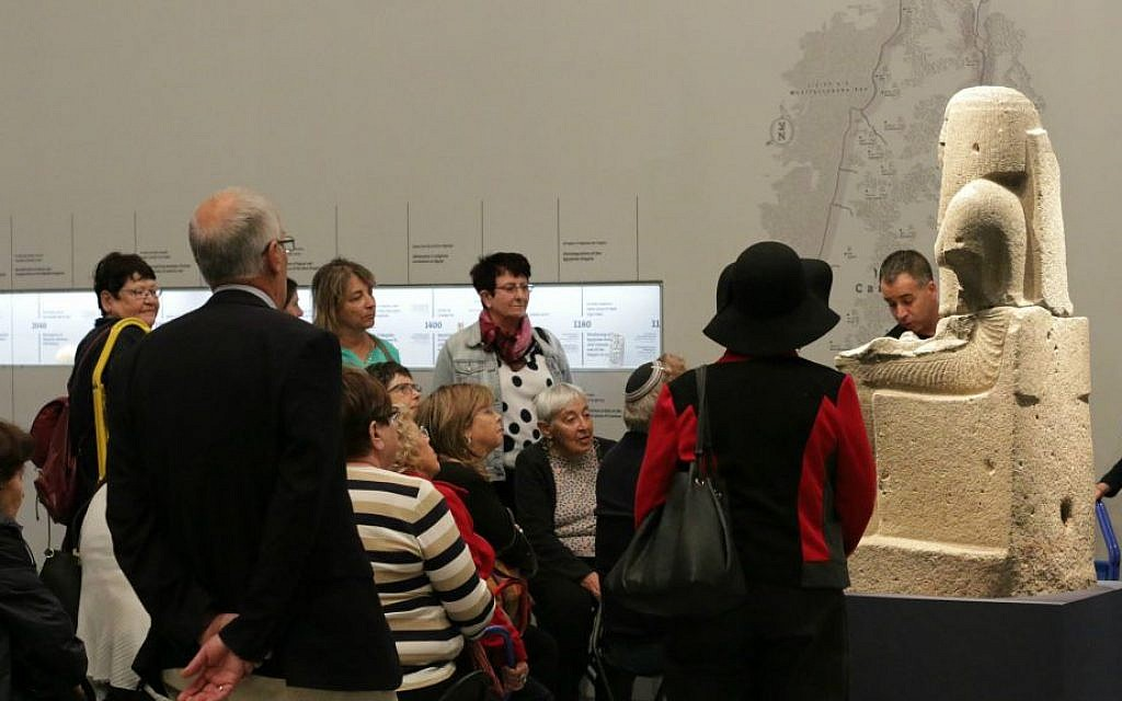 Museum visitors hearing an explanation of the exhibit, with a view of the descriptive index wall that runs the length of the three galleries (Luke Tress/Times of Israel)