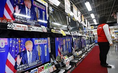 A salesclerk stands in front of flat-panel TVs showing Republican's front-runner candidate Donald Trump in a news program on the US presidential election at an electronics store in Tokyo, March 2, 2016. (AP/Shizuo Kambayashi)