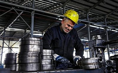 In this Thursday, Feb. 25, 2016 photo, a worker handles steel products at a factory for tubes and pipes in the Muwaqer Industrial Estate, in northern Jordan. The estate is one of five zones in Jordan that would benefit from proposed new trade terms with Europe, part of a precedent-setting plan by Jordan and international donors to put up to 200,000 Syrian refugees in coming years. (AP Photo/Raad Adayleh)