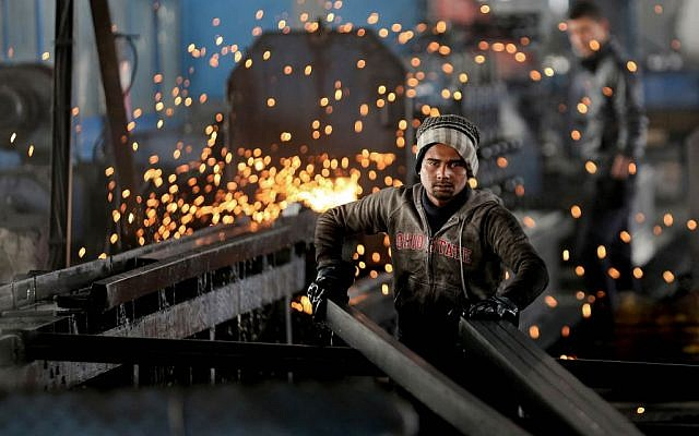 A worker from India arranges steel tubes at a factory in the Muwaqer Industrial Estate, in northern Jordan, February 25, 2016. (AP/Raad Adayleh)