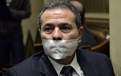 "In this Jan. 12, 2016 file photo, MP Tawfiq Okasha sits in an anteroom after he taped his mouth shut in protest at not being given the floor during a parliamentary session, in Cairo, Egypt. Arabic writing reads, ""Banned from speaking inside and outside the house by government orders."" (AP Photo/Said Shahat, File)"