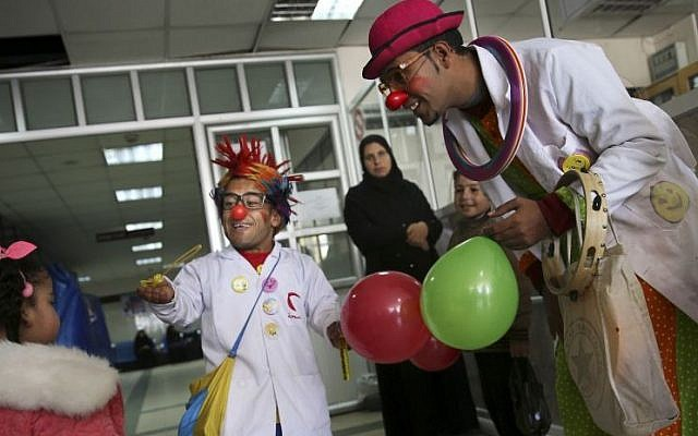 Palestinian medical clowns, 24-year-old Majed Kaloub, right, and 33-year-old Alaa Miqdad, center, entertain children at Al-Rantisi children's hospital in Gaza City, March 17, 2016. (AP/Adel Hana)