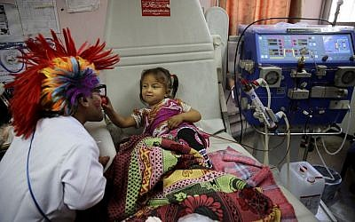 33-year-old Palestinian clown doctor Alaa Miqdad, left, entertains 3-year-old patient Yaqin Shawaf, who suffers from dialysis, in the department of kidney diseases at Al-Rantisi children's hospital in Gaza City, March 17, 2016. (AP/Adel Hana)