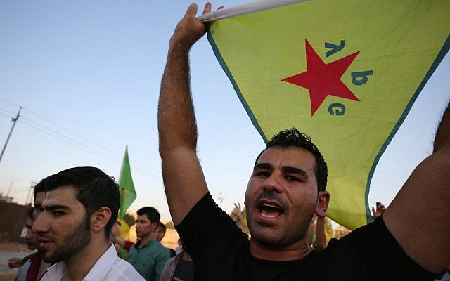 In this Saturday, July 25, 2015 file photo, a demonstrator waves the People's Protection Units flag, known as YPG, which is the main Kurdish fighting force in Syria, during a demonstration in Irbil, the Northern Kurdish region of Iraq. (AP Photo/Bram Janssen)