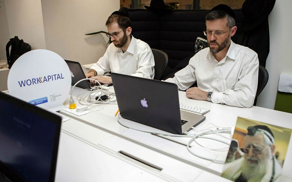 In this photo taken Tuesday, March 15, 2016, ultra-Orthodox Jewish men work at a high tech start-up in an office in Tel Aviv. (AP Photo/Dan Balilty)