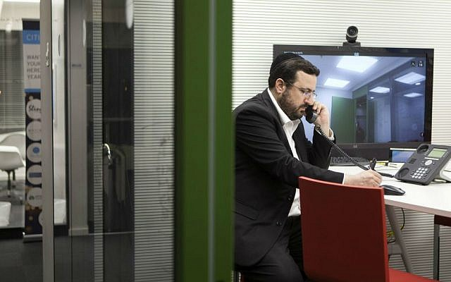 In this photo taken Tuesday, March 15, 2016, Moshe Friedman, a co-founder of KamaTech, speaks on the phone in a high tech start-up office in Tel Aviv. (AP Photo/Dan Balilty)