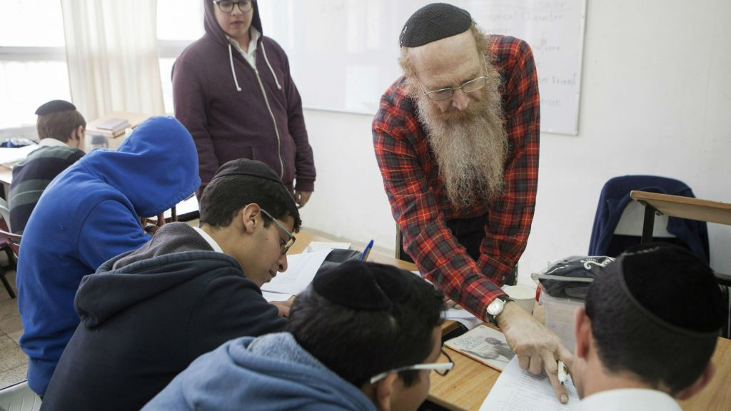 In this photo taken Tuesday, March 15, 2016, a teacher speaks to students during a class at the Yeshiva high school Chachme Lev in Jerusalem. More and more, young ultra-Orthodox insist they can continue to lead pious lives while also embracing technology, the modern workplace and their fellow Israelis. (AP Photo/Dan Balilty)