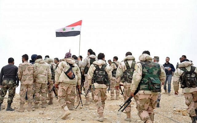 File: Syrian soldiers gather around a Syrian national flag in Palmyra, Syria, after taking the city from Islamic State, March 27, 2016. (SANA via AP)