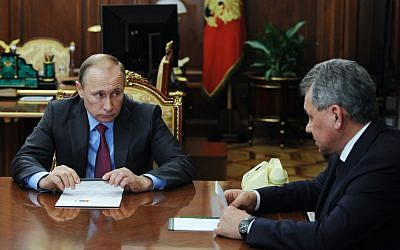 Russian President Vladimir Putin, left, listens to Russian Defense Minister Sergey Shoigu during their meeting in the Kremlin in Moscow, Russia, Monday, March 14, 2016. (Mikhail Klimentyev, Sputnik, Kremlin Pool via AP)