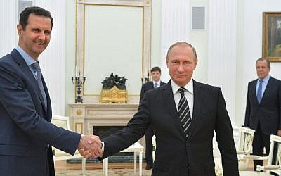 Russian President Vladimir Putin, center, shakes hand with Syrian President Bashar Assad as Russian Foreign Minister Sergey Lavrov, right, looks on in the Kremlin in Moscow, Russia, Tuesday, October 20, 2015. (Alexei Druzhinin, Sputnik, Kremlin Pool Photo via AP, File)