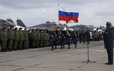 In this photo provided by the Russian Defense Ministry Press Service, guards walk past a lineup of troops during a welcome ceremony for Russian military personnel who returned from Syria at an airbase near the Russian city Voronezh, Tuesday, March 15, 2016. (Russian Defense Ministry Press Service via AP)