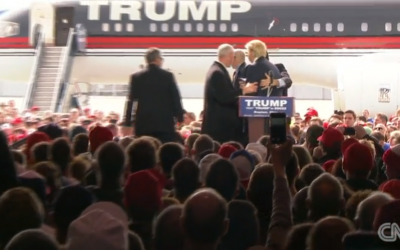 Security guards rush the stage to surround Donald Trump, Dayton, Ohio, March 12, 2016 (CNN screenshot)
