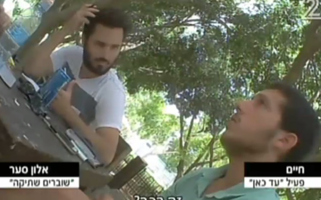 A Breaking the Silence member (left) interviews an Ad Kan activist, posing as a soldier wanting to give testimony, in a Channel 2 report aired on March 17, 2016 (Channel 2 screenshot)