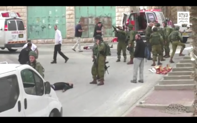 An IDF soldier loading his weapon before he appears to shoot an unarmed, prone Palestinian assailant in the head following a stabbing attack in Hebron on March 24, 2016. (Screen capture: B'Tselem)