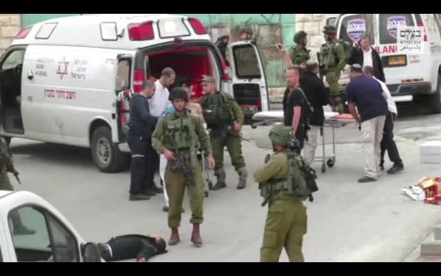 An IDF soldier walks past a disarmed, supine Palestinian assailant moments before he was shot in the head by another soldier following a stabbing attack in Hebron on March 24, 2016. (Screen capture: B'Tselem)