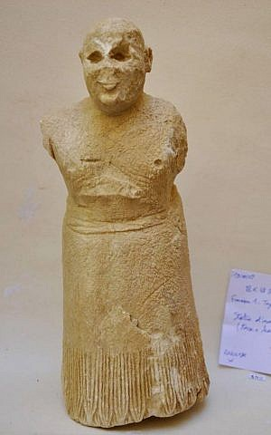 A clay statue of a smiling worshiper dating from nearly 5,000 years ago, discovered in 2009 among a cache of statues buried under a stair in an early 3rd millennium BCE temple in the ancient city of Mari, Syria. (DGAM via AP)