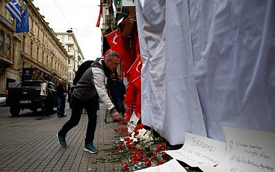 A man leaves carnations at the site of a suicide bombing in Istanbul on Sunday, March 20, 2016, a day after the attack, which killed four, including three Israeli tourists (AP Photo/Emrah Gurel)