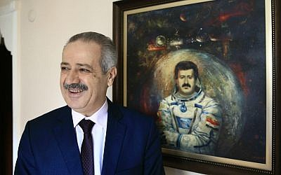 Muhammad Faris, Syria's first cosmonaut and a former general of the Syrian Air Force, backdropped by a paining of him in a space suit, smiles as he poses for the photographer in Istanbul, Monday, March 7, 2016. (AP Photo/Lefteris Pitarakis)