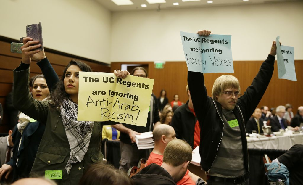 Students hold up protest signs at the end of a public comment period during a University of California Board of Regents meeting Wednesday, March 23, 2016, in San Francisco (AP Photo/Eric Risberg)