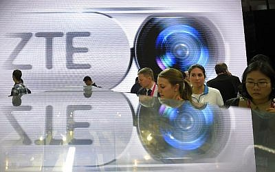 "This file photo taken on February 23, 2016 shows visitors testing smart phones at the ZTE's stand during the Mobile World Congress in Barcelona. The United States said March 7, 2016 it is placing trade restrictions on Chinese telecommunications equipment giant ZTE due to violations of US sanctions on Iran.The Commerce Department said in an order to be officially published on Tuesday that ZTE Corp and related companies set up a scheme to circumvent US sanctions and ""illicitly export"" controlled items to Iran, violating US laws.  / AFP / LLUIS GENE"