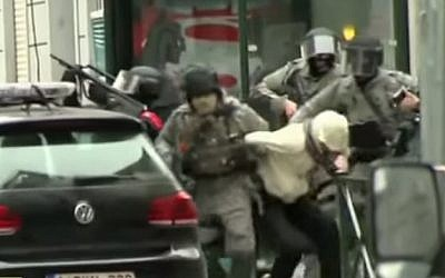 Belgian police arrest a suspect believed to be Paris terror suspect Salah Abdeslam during a raid in the Brussels neighborhood of Molenbeek on March 18, 2016 (screen capture: YouTube)