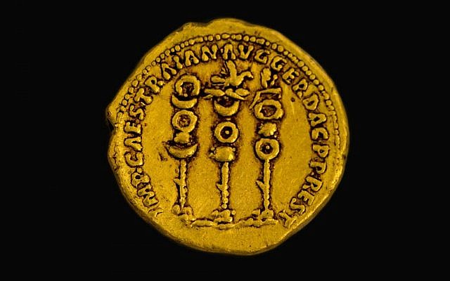 Symbols of the Roman legions next to the name of the ruler Trajan on a 2,000 year old gold coin found in northern Israel. (Samuel Magal, courtesy of the Israel Antiquities Authority)
