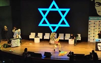 Artist Ariel Bronz getting personal with a flag at a Haaretz conference in Tel Aviv on March 6, 2016. (Screen capture: YouTube/Haaretz)