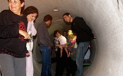 Israeli citizens take cover as a warning siren sounds for possible incoming rockets in Nitzan on November 14, 2012. (Roni Schutzer/Flash90)