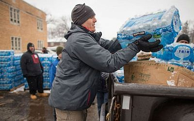 Volunteers loading cases of free water into waiting vehicles at a water distribution center in Flint, Michigan, March 5, 2016. (Geoff Robins/AFP/Getty Images/via JTA)
