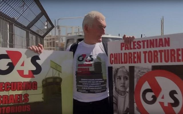 A protester holds posters against the G4S security company outside Israel's Ofer Prison in May 2013 (screen capture: YouTube)