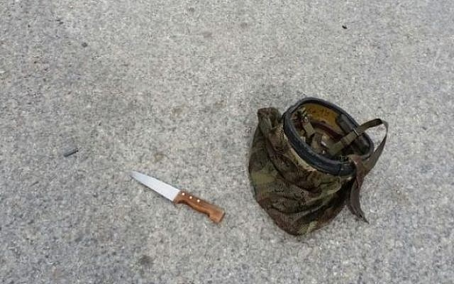 A picture showing the knife allegedly used in a Hebron stabbing attack, next to an IDF helmet, on March 24, 2016. (courtesy)