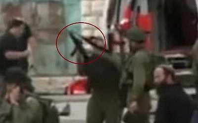 The soldier suspected of shooting a disarmed, wounded Palestinian assailant cocks his weapon (circled in red) moments before allegedly shooting a Palestinian stabber (YouTube screenshot)