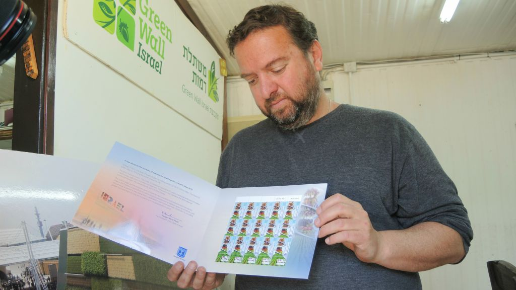 During a tour of the GreenWall greenhouse on March 23, 2016, Barness shows stamps issued by the Israeli government, showing the vertical farm at the 2015 Milan Expo. (Melanie Lidman/Times of Israel)