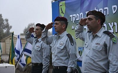 Brig.-Gen. Ofek Buchris, right, salutes during a ceremony to mark his exit as commander of the Bashan Division, along with head of the Northern Command Maj.-Gen. Aviv Kochavi, center, and Brig.-Gen. Yaniv Asur, in September 2015. (IDF Spokesperson's Unit)