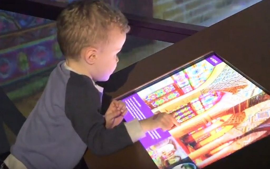 A child enjoys an interactive feature at the 'America to Zanzibar' exhibition at the Children's Museum of Manhattan (screen capture: YouTube)