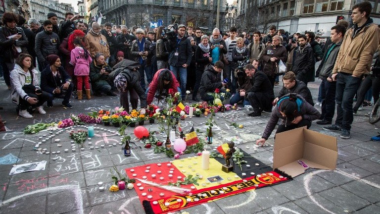 People leave candles and flowers in tribute to victims at a makeshift memorial in front of the stock exchange at the Place de la Bourse (Beursplein) in Brussels on March 22, 2016. (Aurore Belot/Belga/AFP)