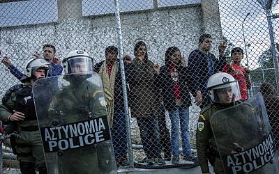 Greek police stand guard in front of the Moria camp while refugees demonstrate against the new deal between EU and Turkey, on March 24, 2016 in Lesbos, Greece. (AFP/Fabio Bucciarelli)