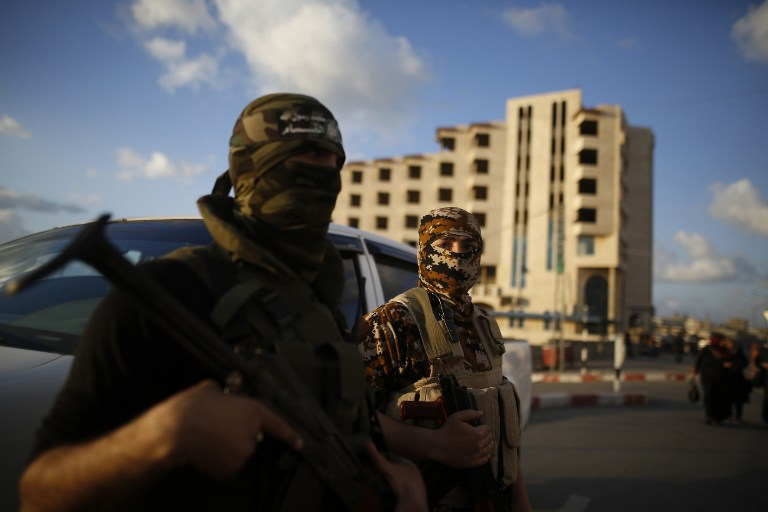 Members of the Izz al-Din al-Qassam Brigades, the armed wing of the Palestinian Islamist movement Hamas, holds his weapon as they guard a street in Gaza City on March 28, 2016. (AFP / MOHAMMED ABED)